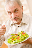 Senior mature man eat vegetable salad Stock Photo