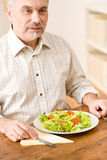 Senior mature man eat vegetable salad Stock Photos
