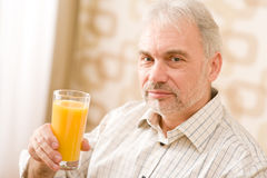 Senior mature man with glass of orange juice Royalty Free Stock Photos