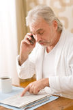 Senior mature man - with newspaper, on phone Royalty Free Stock Photo