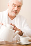 Senior mature man pour coffee wear bathrobe Royalty Free Stock Image