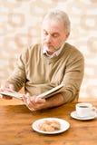 Senior mature man reading book having coffee Stock Image