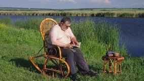 Senior Mature man reading book on rocking on a wicker rocking-chair stock video footage