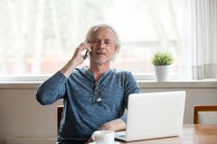 Senior mature man talking on phone making call at home. Senior mature retired man talking on the phone making call sitting with laptop, old middle aged elderly royalty free stock images