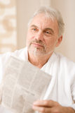 Senior mature man thoughtful read newspaper Royalty Free Stock Photos