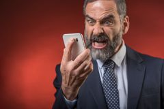 Stressful news for a senior business man. Senior mature man yelling at his cell phone, furious and enraged, red background Stock Photography