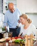 Senior with mature wife smiling and preparing food Stock Image