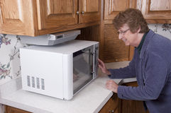 Senior Mature Woman Cooking Microwave Oven Kitchen. Smiling senior mature woman and grandma is cooking dinner with her modern microwave oven while in her kitchen Royalty Free Stock Photo
