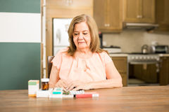 Senior mature woman looking at her medicines Royalty Free Stock Photography