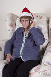 Senior Mature Woman Mad Angry Unhappy Cell Phone. Senior mature woman mad, angry, unhappy, wearing Santa Claus hat at Christmas. Grandma is talking on a cell Royalty Free Stock Photography