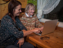 Senior and mature women using a laptop. Senior and mature women having fun using a laptop. They are sitting on a wooden table in a small living room in the Royalty Free Stock Photo