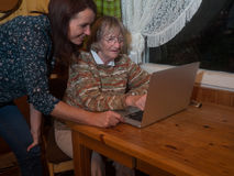 Senior and mature women using a laptop. Senior and mature women having fun using a laptop. They are sitting on a wooden table in a small living room in the Royalty Free Stock Image