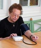 Senior measure blood pressure. An old woman measured her blood pressure stock images
