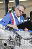 Senior mechanic analyzing car engine and holding clipboard Stock Image