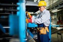 Senior Mechanic Repairing Machine Units at Factory Stock Image