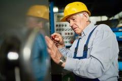 Senior Mechanic Repairing Machines at Factory Stock Photos