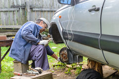 Senior mechanic replaces the vehicle's front wheel. Royalty Free Stock Image