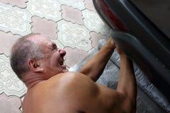 Senior mechanic working under a car Stock Photos