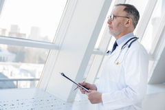 Senior medical specialist holding documents. Thoughtful mature doctor is looking at window pensively. He is standing and holding folder of papers Stock Images