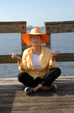 Senior meditation. A senior woman sitting on a dock in a meditation pose royalty free stock photography