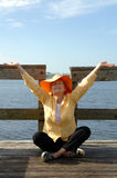 Senior meditation/praise. A senior woman sitting on a dock in a meditation pose stock images