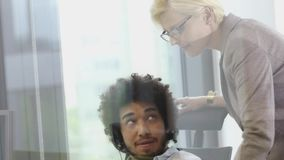 Senior member of staff working with middle eastern man in call centre office with headsets stock footage