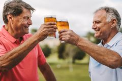 Senior men celebrating with beers. Two senior men toasting beer glasses outdoors. Smiling mature male friends cheering beers while standing outside royalty free stock images