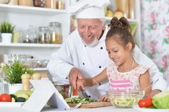 Man preparing dinner with granddaughter Royalty Free Stock Photo
