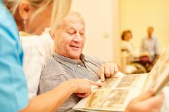 Senior man with dementia looks at photos. Senior men with dementia looks at photos together with caregiver in nursing home stock images