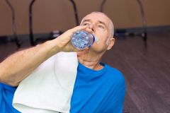 Senior man drinking water in gym. Senior men drinking water in the gym Stock Image