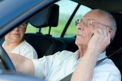 Senior man driver calling at same time Stock Images