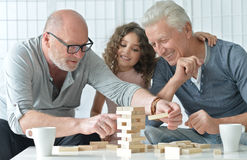 Senior men and granddaughter with  board game Stock Image