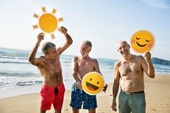 Senior men having fun on the beach. With emoji royalty free stock image