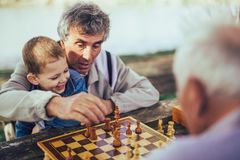Senior men having fun and playing chess at park. Active retired people, old friends and free time, two senior men having fun and playing chess at park, spend royalty free stock image