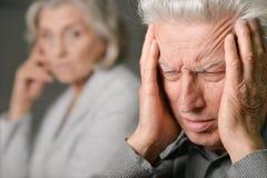 Senior man with headache holding Royalty Free Stock Photo