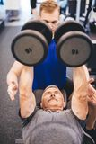 Senior man lifting weights assisted by gym instructor Stock Photos