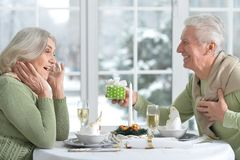 Senior man making a surprise to his wife. Senior men making a surprise to his wife present  a gift Royalty Free Stock Image