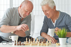 Senior men playing chess. Two senior men having fun and playing chess at home royalty free stock images