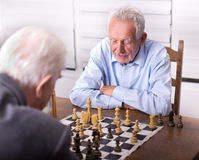Senior men playing chess. Two senior men playing chess in the room Stock Image