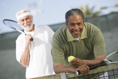 Senior Men Playing Tennis. Portrait of senior African American men with friend playing doubles stock photos