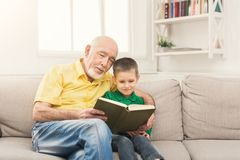 Senior man reading book for his grandchild. Senior men reading book for his grandchild. Cheerful grandfather telling fairy tale aloud to his excited grandson royalty free stock image