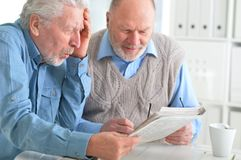 Senior men reading newspaper. Two senior men sitting at table and reading newspaper royalty free stock photography