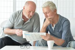 Senior men reading newspaper. Two senior men sitting at table and reading newspaper royalty free stock image