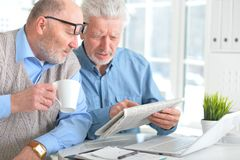 Senior men reading newspaper. Two senior men sitting at table and reading newspaper stock photo