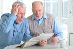 Senior men reading newspaper. Two senior men sitting at table and reading newspaper stock photography