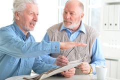 Senior men reading newspaper. Two senior men sitting at table and reading newspaper royalty free stock images