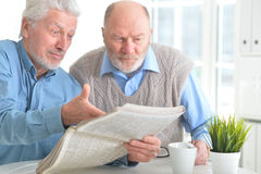 Senior men reading newspaper. Two senior men sitting at table and reading newspaper royalty free stock photos