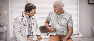 Senior man showing stomach ache pain to doctor. Senior men showing stomach ache pain to doctor in clinic royalty free stock image