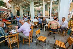 Senior men sitting around tables and talking in rustic cafe of village Stock Image
