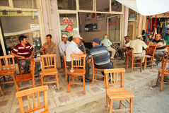 Senior men sitting around tables and talking in rustic cafe of village Stock Photos